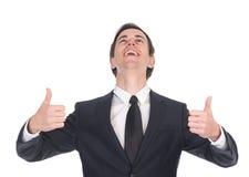 Бизнесмен смеясь над и показывая большими пальцами руки вверх стоковое изображение