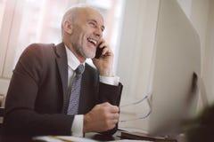 Бизнесмен смеясь над на телефоне стоковые изображения