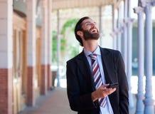 Бизнесмен смеясь над с мобильным телефоном outdoors стоковое изображение rf