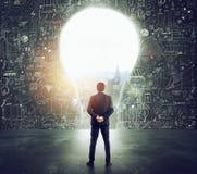 Бизнесмен смотрит большое отверстие на стене сформированной как электрическая лампочка стоковое фото rf