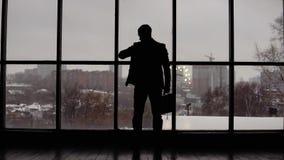 Бизнесмен смотрит время на наручных часах в офисе около окна видеоматериал