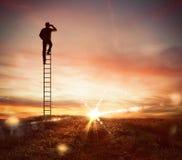Бизнесмен смотрит далеко для нового дела с бинокулярным стоковое фото rf