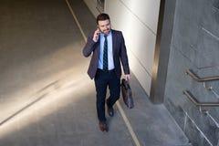 Бизнесмен смотрит его мобильный телефон Стоковые Фото