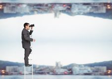 Бизнесмен смотря далеко с биноклями близко к городу стоковые фото