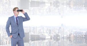 Бизнесмен смотря вверх ногами город через бинокли Стоковое Изображение