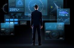 Бизнесмен смотря виртуальный экран от задней части Стоковая Фотография
