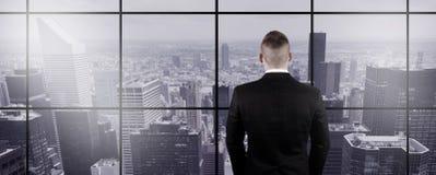 Бизнесмен смотря вне окно Стоковые Фото