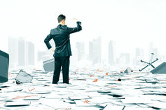 Бизнесмен смотря горизонт среди хаоса вещества офиса стоковое фото