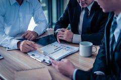 Бизнесмен 3 смотря диаграмму в бумаге и беседе о бизнес-плане, маркетинг и финансовое в будущем стоковая фотография rf