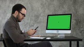 Бизнесмен смотря его послание смартфона и сидя около экрана компьютера Зеленый дисплей модель-макета экрана сток-видео