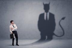 Бизнесмен смотря его собственную концепцию тени демона дьявола Стоковое Изображение