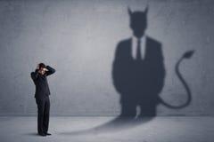 Бизнесмен смотря его собственную концепцию тени демона дьявола Стоковое фото RF
