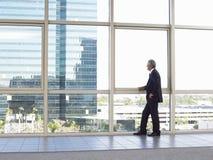 Бизнесмен смотря из окна офиса Стоковая Фотография