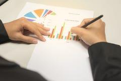 Бизнесмен смотря и писать на предпосылке диаграмм дела, диаграмм и документов для анализировать дело Стоковое фото RF