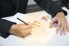 Бизнесмен смотря и писать на предпосылке диаграмм дела, диаграмм и документов для анализировать дело Стоковые Фото