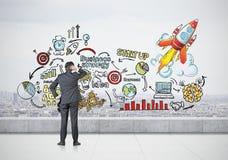 Бизнесмен смотря красочный startup эскиз на крыше Стоковое Изображение