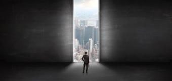 Бизнесмен смотря к городскому пейзажу от темной пустой комнаты стоковые изображения rf
