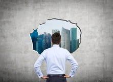 Бизнесмен смотря к городу Стоковая Фотография