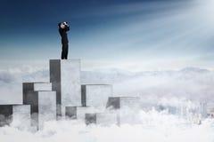 Бизнесмен смотря небо с биноклями Стоковые Изображения