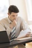 Бизнесмен смотря документы пока сидящ на столе в офисе Стоковое Изображение RF