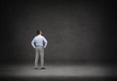 Бизнесмен смотря предпосылку бетонной стены Стоковые Изображения