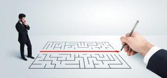 Бизнесмен смотря решение под рукой чертежа для лабиринта Стоковая Фотография RF