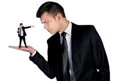 Бизнесмен смотря сердитый на маленьком человеке стоковая фотография