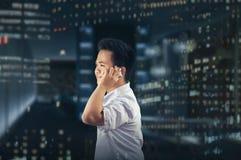 Бизнесмен смотря счастливый пока вызывающ кто-то на мобильном телефоне Стоковые Изображения