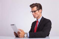 Бизнесмен смотря таблетку Стоковое Изображение