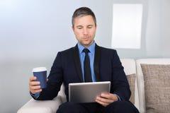 Бизнесмен смотря цифровую таблетку Стоковые Фото