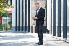 Бизнесмен смотря цифровую таблетку Стоковые Фотографии RF