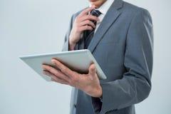 Бизнесмен смотря цифровую таблетку Стоковая Фотография
