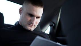 Бизнесмен смотря через документы пока сидящ на задней части автомобиля стоковое фото