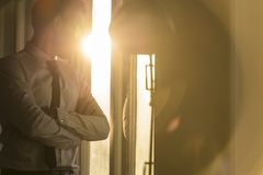 Бизнесмен смотря через окно на заходе солнца стоковые изображения