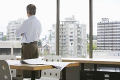 Бизнесмен смотря через окно офиса Стоковые Фото
