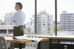 Бизнесмен смотря через окно офиса Стоковая Фотография RF