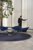 Бизнесмен смотря через шторки в лобби офиса Стоковая Фотография RF