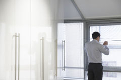 Бизнесмен смотря через шторки Стоковое Изображение RF