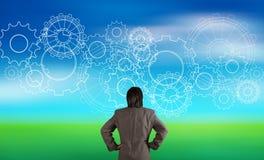 Бизнесмен смотря шестерню к концепции успеха Стоковое фото RF