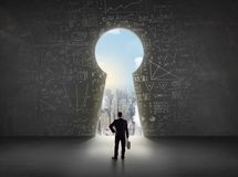 Бизнесмен смотря keyhole с яркой концепцией городского пейзажа Стоковое Изображение