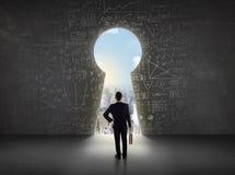 Бизнесмен смотря keyhole с яркой концепцией городского пейзажа Стоковые Фото