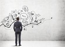 Бизнесмен смотря startup значки и диаграммы на бетонной стене Стоковые Фотографии RF
