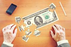 Бизнесмен собирает 100 американских долларов как головоломки Стоковые Фото