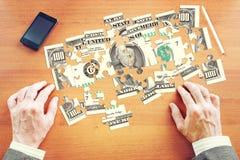 Бизнесмен собирает 100 американских долларов как головоломки Стоковая Фотография RF