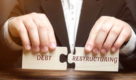 Бизнесмен собирает деревянные блоки с реструктуризацией долгов слова Частичное списание задолженности Изменяя условия погашения з стоковое изображение rf