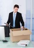 Бизнесмен собирая канцелярские товар в картонной коробке на столе Стоковые Изображения