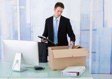 Бизнесмен собирая канцелярские товар в картонной коробке на столе Стоковая Фотография