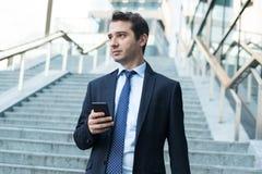 Бизнесмен со смартфоном идя в улицу города стоковые изображения rf