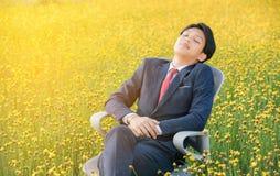 Бизнесмен спать в поле цветка Стоковая Фотография RF