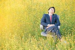 Бизнесмен спать в поле цветка Стоковое фото RF